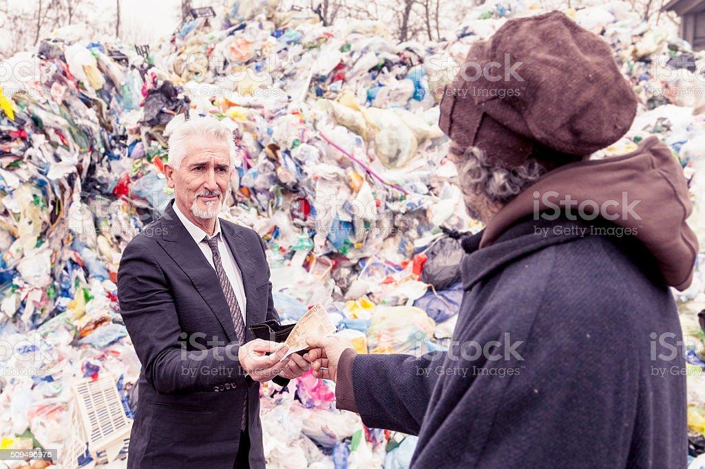 Geschäftsmann bietet Mittel obdachlos Mann in ein Müllkippe – Foto