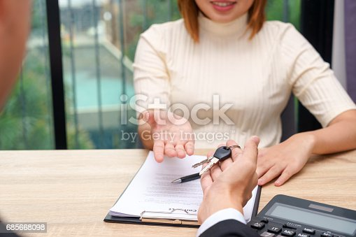 istock Businessman giving a house key or car key in font of loan contract. 685668098