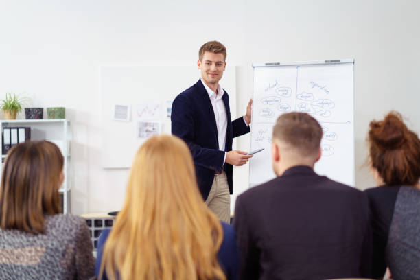 Businessman giving a presentation to an audience stock photo
