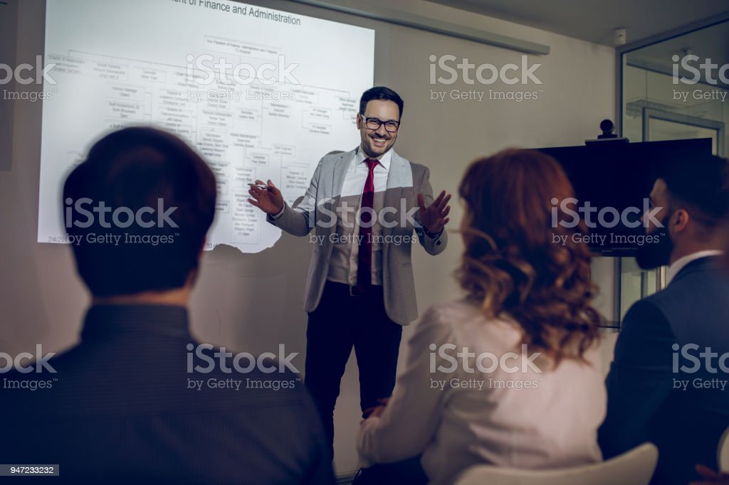 Businessman giving a presentation to his team stock photo
