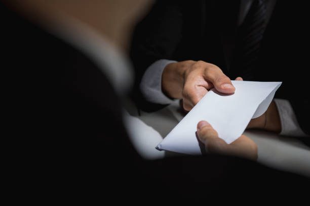 businessman giving bribe money in the envelope to partner - money black background stock photos and pictures