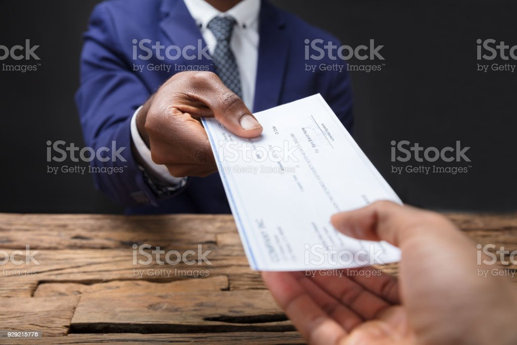 Businessman Giving Cheque To His Colleague stock photo