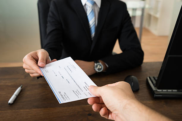 businessman giving cheque to other person - wages stock photos and pictures