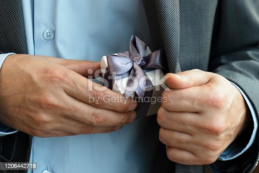 Chest view of an unrecognizable businessman wearing a suit who is about to give a gift box out of his jacket. The white gift box is wrapped with purple ribbon.