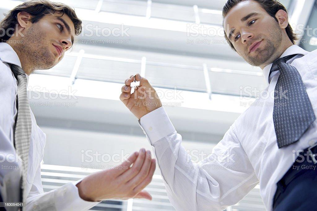 Businessman giving key stock photo