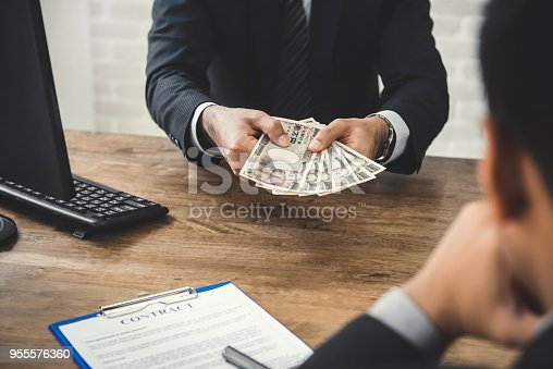 istock Businessman giving money, Japanese yen banknote, to his partner while making contract 955576360