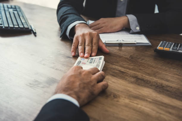 Businessman giving money, Japanese yen banknotes, to his partner Businessman giving money, Japanese yen banknotes, to his partner at the table while making contract - loan, bribery and corruption concepts borrowing stock pictures, royalty-free photos & images