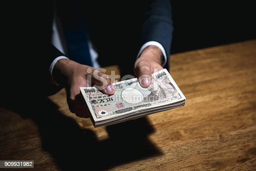 istock Businessman giving money, Japanese yen currency, in dark room 909931982