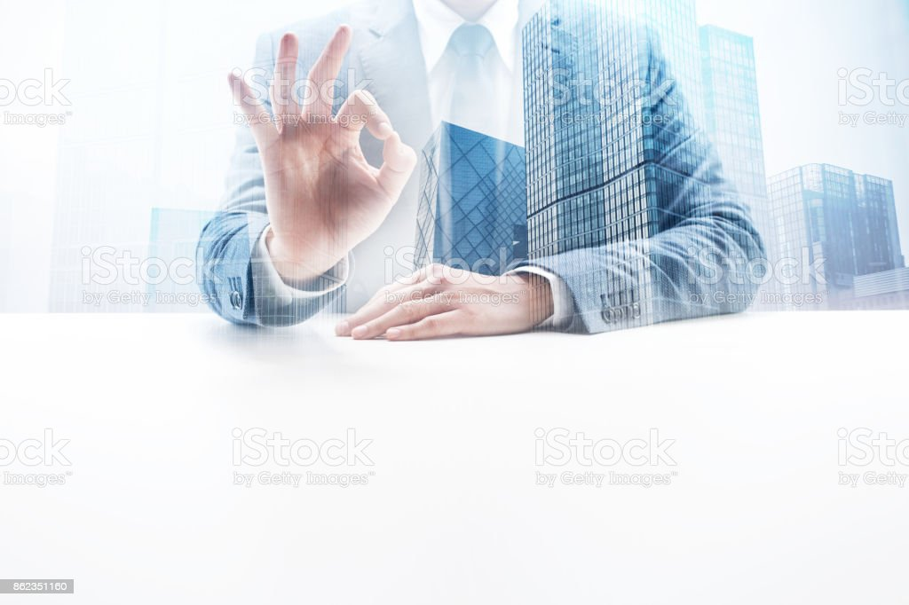 Businessman Giving Okay Sign with Double Exposure Cityscape stock photo