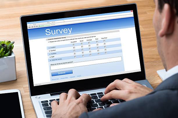 Businessman Giving Online Survey On Laptop stock photo