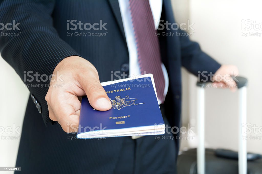 Businessman giving passport with boarding  pass inside stock photo