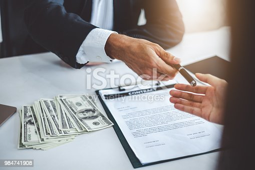 638881988istockphoto Businessman giving pen to businesswoman for signing contract banking money loaning 984741908