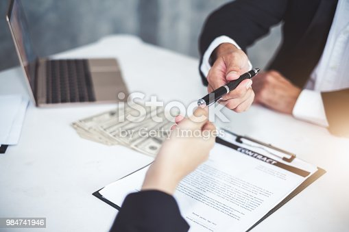 638881988istockphoto Businessman giving pen to businesswoman for signing contract banking money loaning 984741946