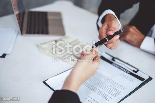 638881988istockphoto Businessman giving pen to businesswoman for signing contract banking money loaning 995971418
