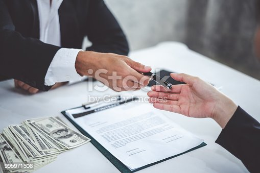 638881988istockphoto Businessman giving pen to businesswoman for signing contract banking money loaning 995971506