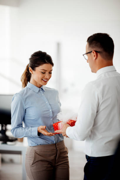 Businessman giving present to his female coworker stock photo stock photo