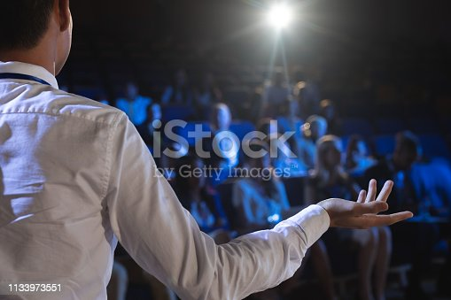 1133973551 istock photo Businessman giving presentation in front of audience in auditorium 1133973551