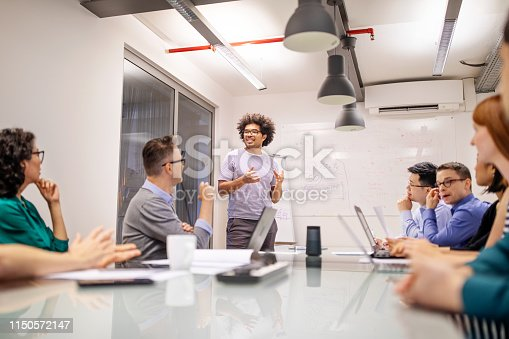 Afro american businessman giving presentation to team in conference room. Diverse group of business people during a strategy meeting in board room.