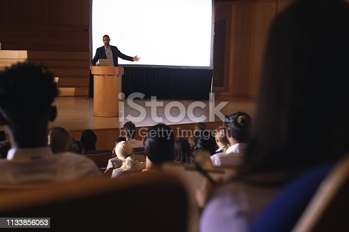 1133973551 istock photo Businessman giving presentation on white projector in front of the audience 1133856053
