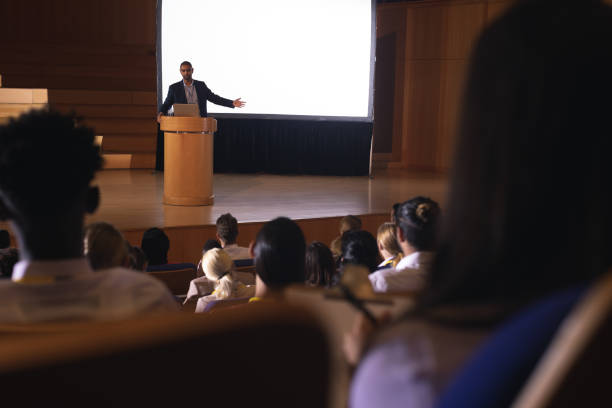 Businessman giving presentation on white projector in front of the audience Front view of mixed race businessman giving presentation on white projector in front of the audience speech stock pictures, royalty-free photos & images