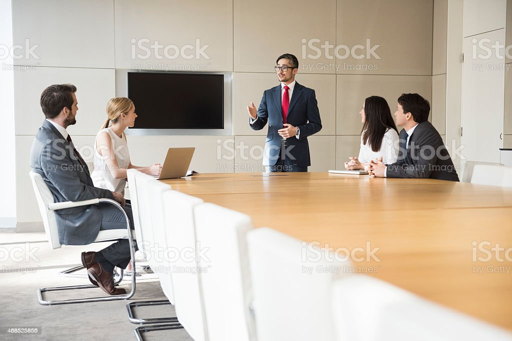 Businessman Giving Presentation To Colleagues At Conference Table stock photo