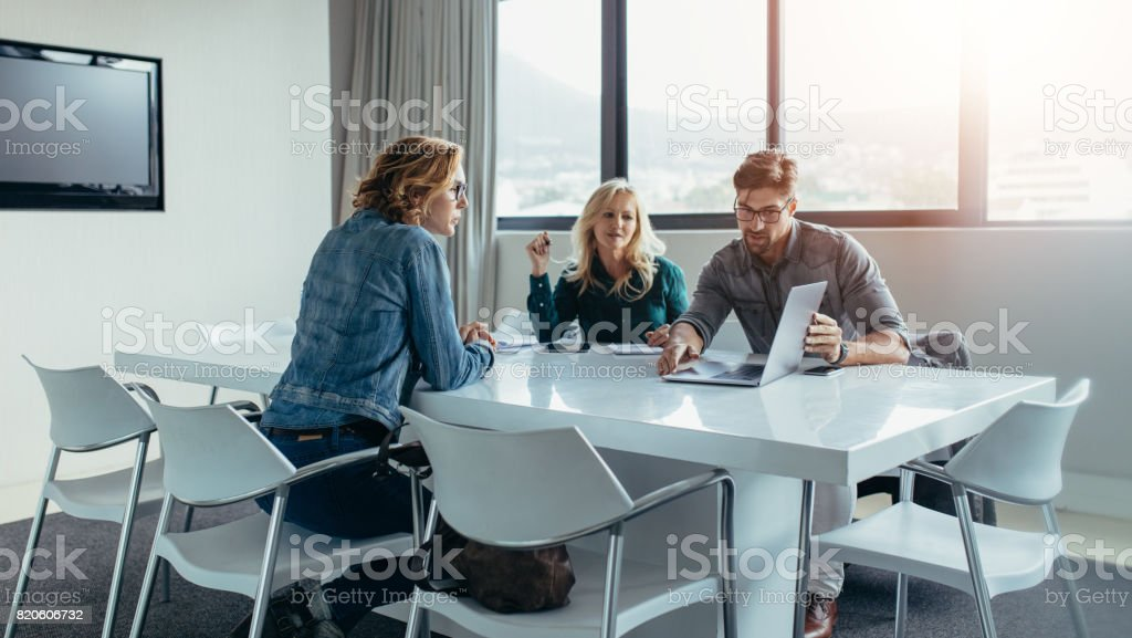 Businessman giving presentation to colleagues at meeting stock photo