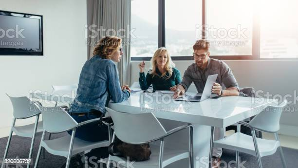 Businessman Giving Presentation To Colleagues At Meeting Stock Photo - Download Image Now