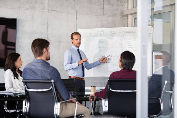 Businessman giving presentation with colleagues Mature businessman giving presentation to his colleagues in modern office. Formal leader presenting new project to business partners in conference room using white board. Businessman in a meeting showing business progressions in boardroom. staff meeting stock pictures, royalty-free photos & images