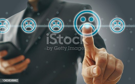istock Businessman giving rating with sad icon 1063838862