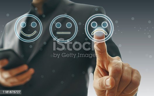 istock Businessman giving rating with sad icon 1181875727