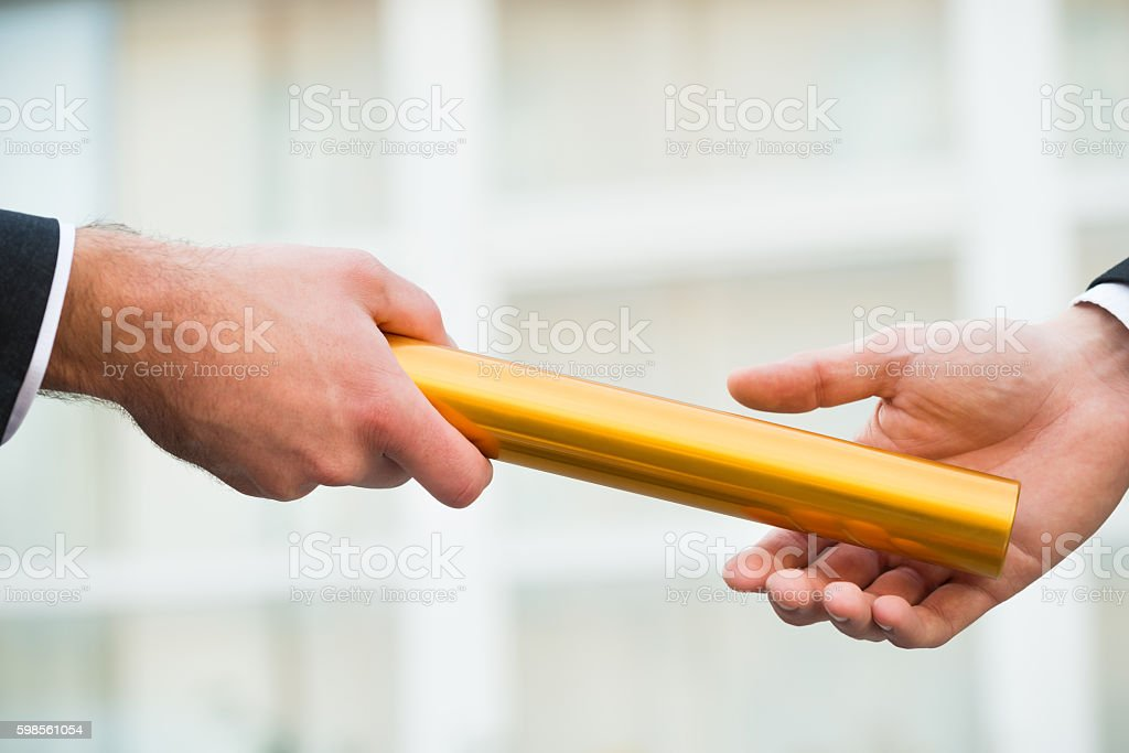 Businessman Giving Relay Baton To Colleague stock photo