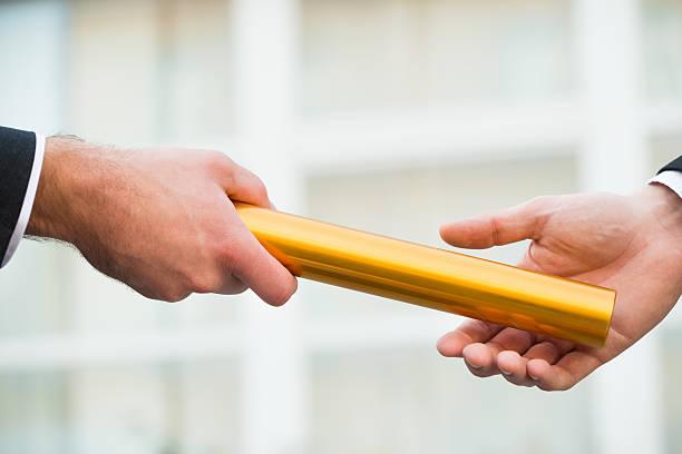 businessman giving relay baton to colleague - staffelstab stock-fotos und bilder