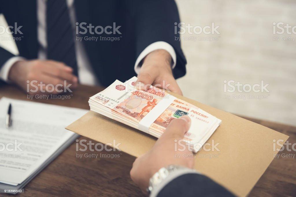 Hombre de negocios dando dinero de Rublo ruso a su pareja - foto de stock