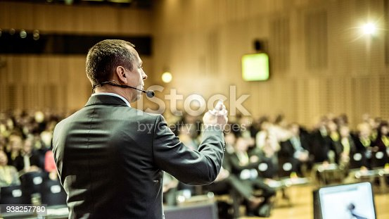 938409136 istock photo Businessman givng lecture at a full conference hall 938257780