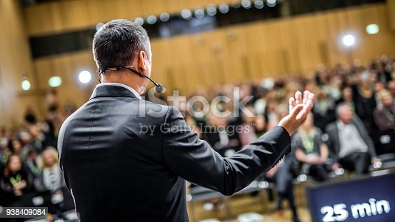 938409136 istock photo Businessman givng lecture at a full conference hall 938409084
