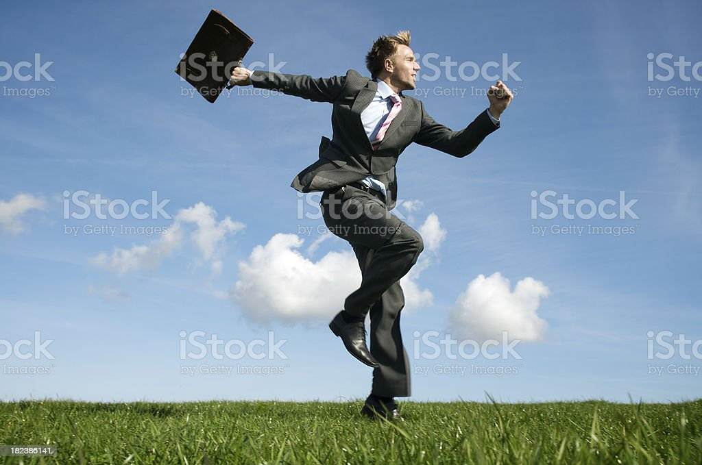Businessman Goes Skipping across Green Meadow stock photo
