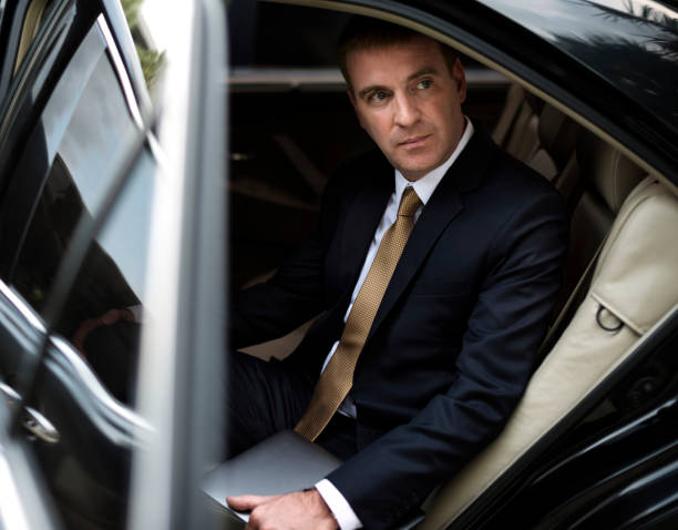 businessman going out of his car - limousine service stock photos and pictures