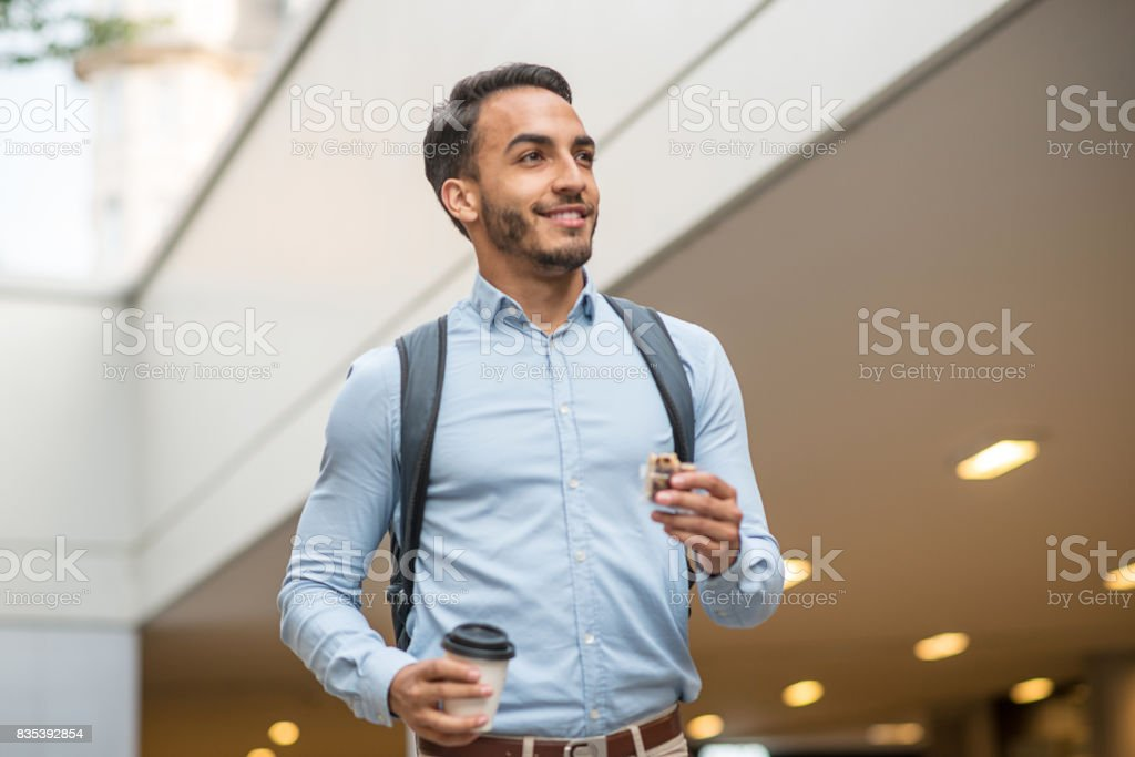 Businessman going to work and eating choco snack stock photo