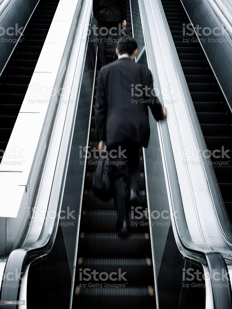 Businessman Going up an Escalator stock photo