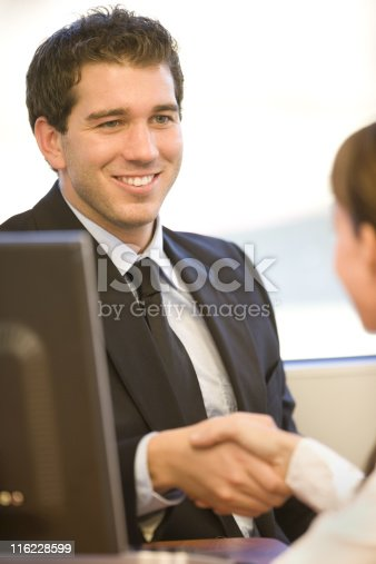 A photo of a young businessman greeting a customer.