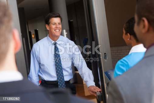 Businessman greeting employees moving in to new office building