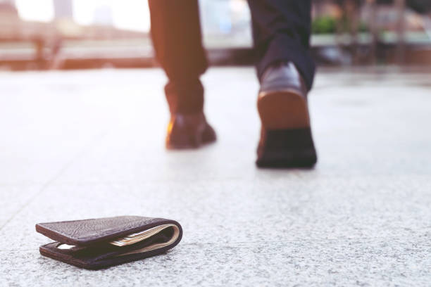 empresário tinha perdido carteira de couro com dinheiro na rua. close-up da carteira que encontra-se no passeio dentro durante o desengate ao trabalho. - parte inferior - fotografias e filmes do acervo