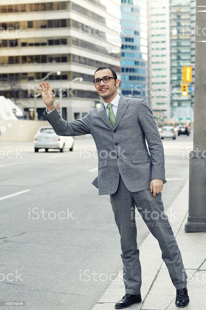 Businessman hailing a cab smiling royalty-free stock photo