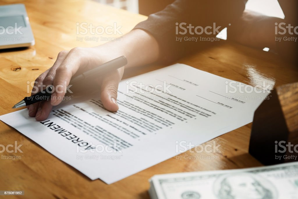 Businessman hand and contract agreement paper with customer to sign contract. Real Estate and Agreement concept. stock photo