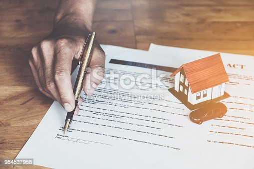 istock Businessman hand and contract agreement paper with customer to sign contract. Real Estate and Agreement concept. 954537958