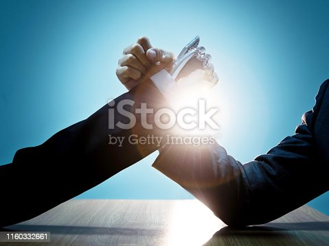 1050855372 istock photo Businessman hand and robot doing arm wrestling 1160332661