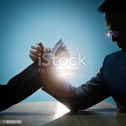 1050855372 istock photo Businessman hand and robot doing arm wrestling 1160333162