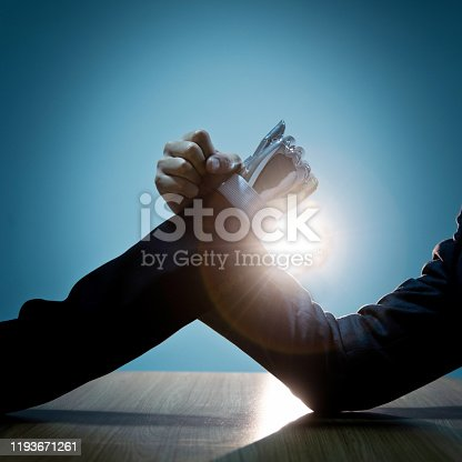 1050855372 istock photo Businessman hand and robot doing arm wrestling 1193671261