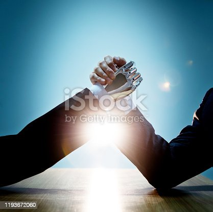1050855372 istock photo Businessman hand and robot doing arm wrestling 1193672060