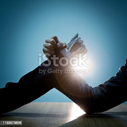 1050855372 istock photo Businessman hand and robot doing arm wrestling 1193679858